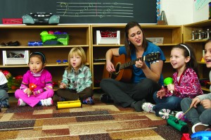 Photo of TCMPS after school music program teacher playing guitars and singing with students