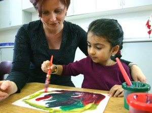 Photo of TCMPS after school Arts program teacher painting with a student