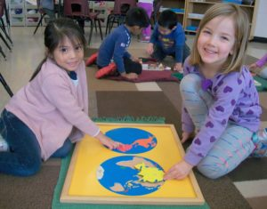 Pre-School students working with the Geography puzzle.