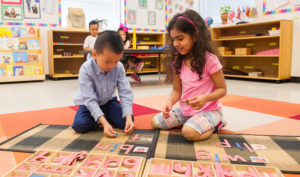 Pre-School students working with large movable alphabet