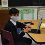 Grade 8 student working on his laptop