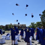 Grade 12 throwing their caps at outdoor graduation ceremony.